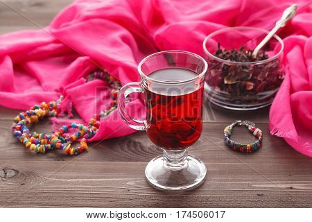 Red Hot Hibiscus Tea In A Glass Mug On A Wooden Table And Dry Tea Custard