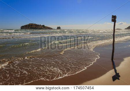 Gargano coast: Portonuovo or Gattarella seascape,Vieste-(Apulia) ITALY-.Sandy beach during a storm: summer wooden signpost on the shore.