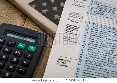 Tax preparation forms and tax tables with calculator on wooden board