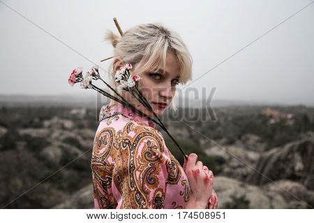 Very pretty Russian young girl with bloody white flowers in the field. She is blonde and her eyes are clear. She is dressed like a Chinese girl and the aesthetics is dark.