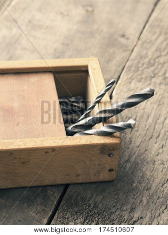 Old used drills in a wooden box on a workbench