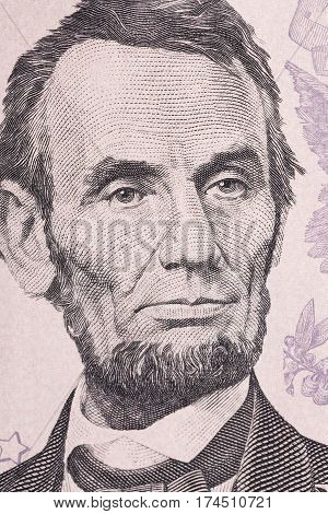 Vertical portrait of Abraham Lincoln's face on the US 5 dollar bill. Macro shot.