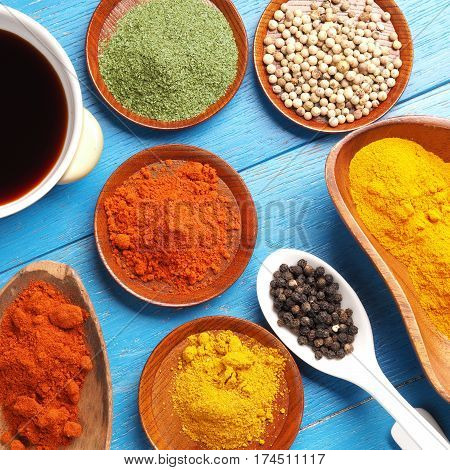 Colorful assortment of herbs and spices on a blue wooden table top view