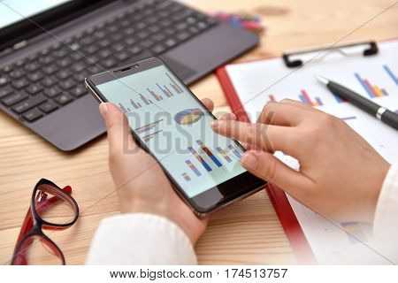 Businesswoman Analyzing Chart On Cellphone, close up
