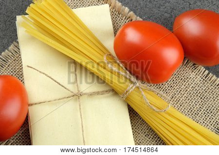 Basic ingredients for cooking Italian pasta: fresh red tomatoes bavette and sheets of lasagne on sackcloth and dark background.