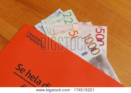 Stockholm Sweden - March 3 2017:The orange envelope from the Swedish Pensions Agency (Pensionsmyndigheten) with teh annual statement on top of Swedish banknotes.