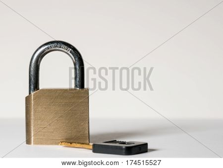 Close shot of a solid brass padlock with hardened hasp with key laying on surface