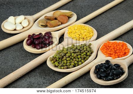 Dried black red white broad beans and red green and yellow lentils on wooden spoons on a dark table.