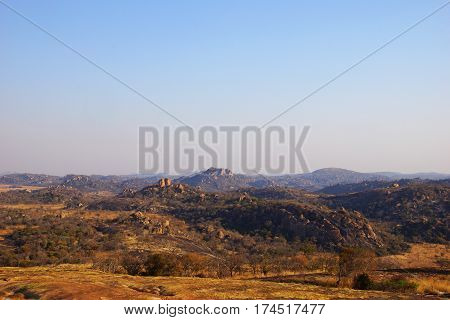 a wide panorama of the national park Matopos-Rhodes in Zimbabwe with the typical rock structures of naked big stones and some hills like also orange-red bushes
