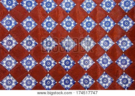 Geometric pattern of hand made ceramic tiles embedded in a wall. Suitable as background