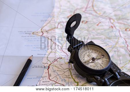 still life with a compass and over a map. travel. journey. direction.