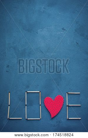 Abstract texture of concrete and blue paint plaster. On the texture matches arranged in the form of the word Love. In the middle of the letters have a wooden red heart.Space for text on a vertical photo. Valentine's Day. World day of the match.