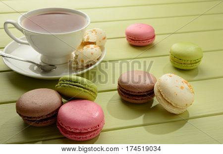 Tasty varicolored macarons and cup of tea on a green wooden table.