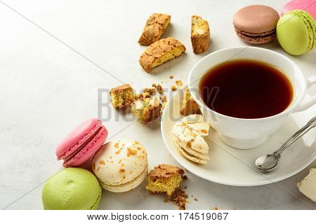 Cup of black tea with tasty almond cookies rich in vitamins minerals and varicolored macaroons on a white background in light key. Copy space.