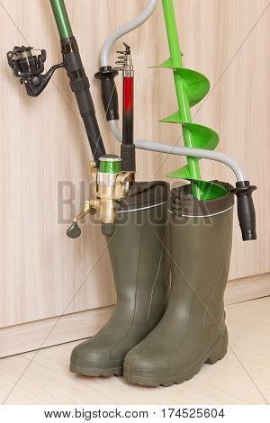Fishing concept: fishing rods and hand ice drill in rubber boots