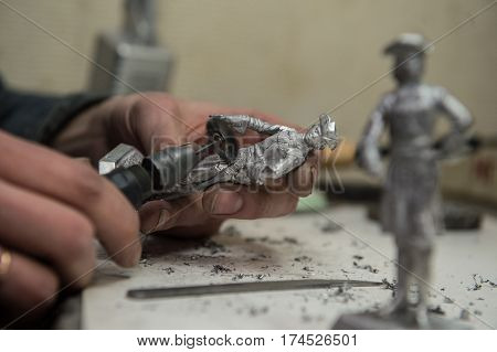 Saint-Petersburg Russia - February 21 2017: A small factory producing small batches pewter figurines. The master cleanse warrior figurine from burrs