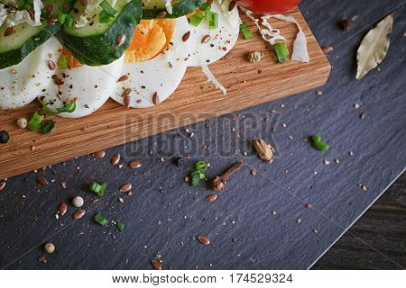 Healthy food and ingredients with tomato cucumber cabbage green onion egg and spices on dark background. Cooking concept.