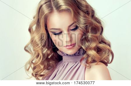Smiling Beautiful girl light brown hair with an elegant hairstyle , hair wave ,curly hairstyle