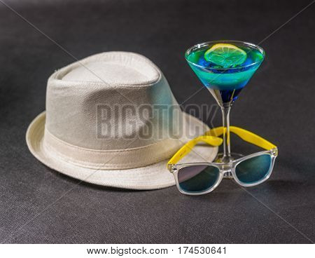 colored drink a combination of blue and green lemon martini glass yellow sunglasses white hat party set