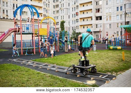 MOSCOW, RUSSIA - JUN 27, 2016: Cameraman and assistant prepare shooting reportage from children playground in courtyard at residential houses.
