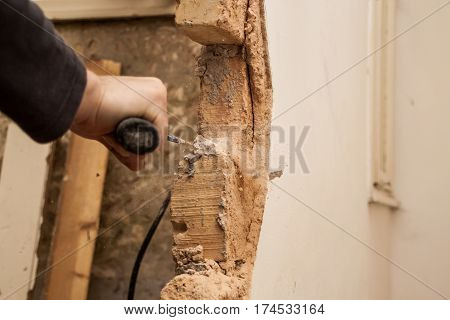 Flat Renovation, Master Mason With A Hammer, With A Pointy Tip Of Trying To Break A Brick Out Of The