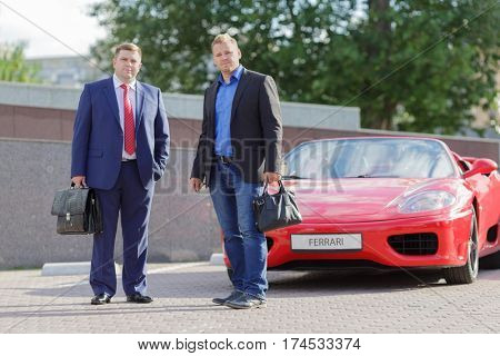 MOSCOW, RUSSIA - JUN 22, 2016: meeting of two mature business people  outside, standing next to luxury supercar Ferrari