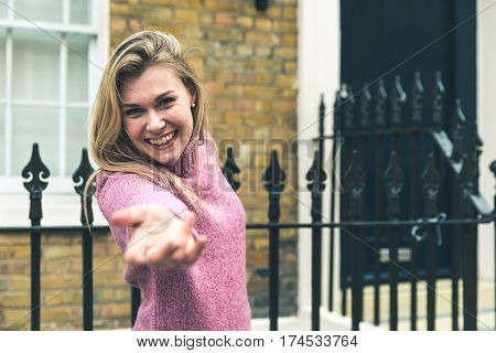 Smiling woman reaching out with her hand. Beautiful blonde girl holding to a railing looking at camera while giving her hand. London typical house on background