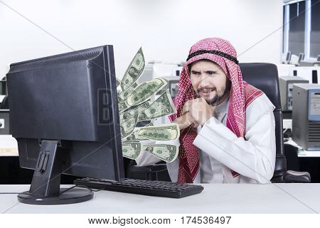 Image of pensive Arabian businessman looking money out of his computer in the workplace