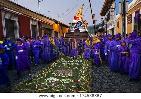 Antigua Guatemala - April 16 2014: Man wearing purple robes carrying a float (anda) during the Easter celebrations in the Holy Week in Antigua Guatemala.