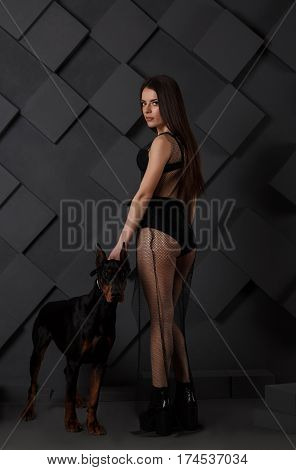 Young sexy brunette in undewear with angry doberman dog looking at the camera