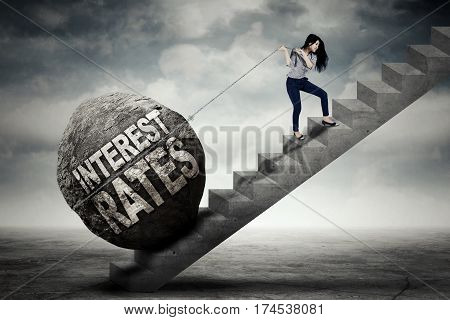 Young businesswoman is pulling big stone with text of interest rates while climbing on the stair