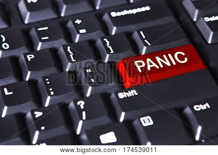 Close up of computer keyboard with panic word on the red button