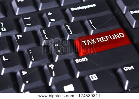 Close up of computer keyboard with text of tax refund on the red button