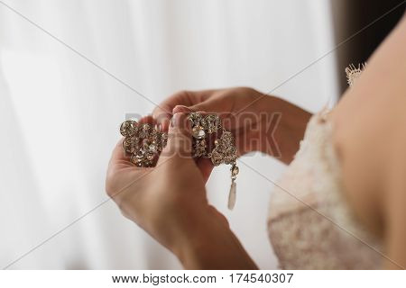 Bride in white dress holding earrings. White background. Close-up. Silver earrings in her hands.