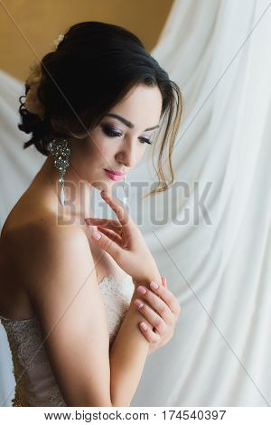 Portrait of a beautiful bride. Bride waiting for the groom. White background. Eyes downcast. The big silver earrings. Female portrait in bridal gown for marriage. Cute lady indoors