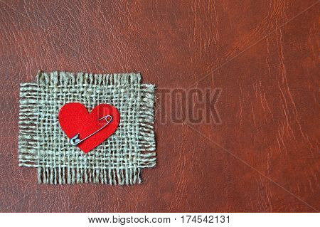 Heart attached on canvas with safety pin drown leather background