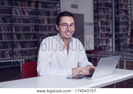 Young entrepreneur university student smiling and working on laptop with book on the scientific thesis in a library