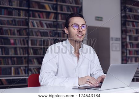 Young entrepreneur university student working on laptop with book on the scientific thesis in a library
