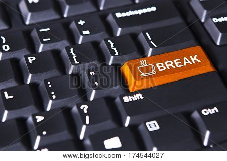 Close up of computer keyboard with break word and coffee on the orange button