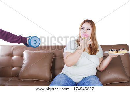 Overweight woman sitting on the sofa while eating donuts and refuse to workout with dumbbell
