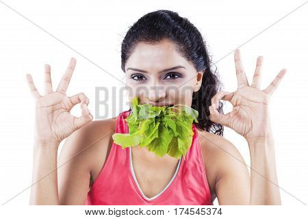 Young Indian woman biting leaves of spinach in her mouth while showing OK sign and looking at the camera in the studio