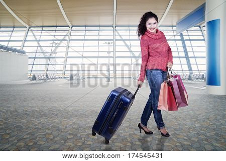 Pretty Indian woman smiling at the camera while wearing winter clothes in the airport terminal and carrying a luggage with shopping bags
