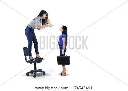 Picture of young leader shouting to her subordinate with a megaphone while standing on the chair isolated on white background