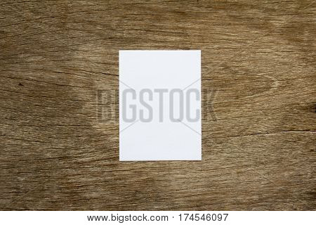 Blank white note paper on brown wooden background for memo or remind