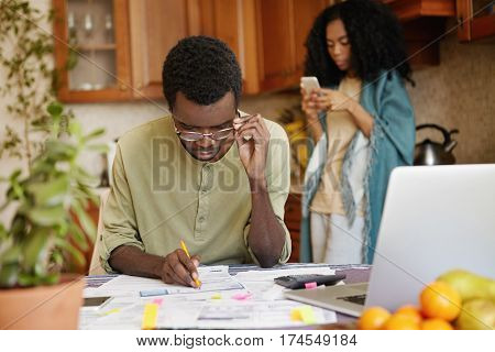 Concentrated Young African Male Filling In Papers, Adjusting His Glasses While Managing Finances And