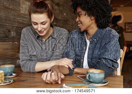 Interracial Happy Lesbian Couple Relaxing At Cafe. Redhead Caucasian Woman Holding Hand Of African-a