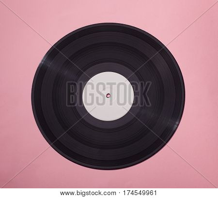 black vinyl disс isolated on pink background with blank white area in center
