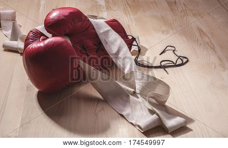 boxing-glove with white old hand-wrap on wooden surface
