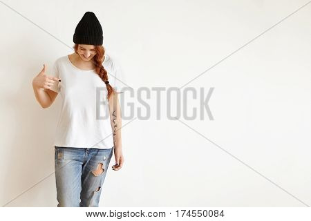 Isolated Studio Shot Of Fashionable Young Caucasian Female With Braid Wearing Stylish Clothes, Looki