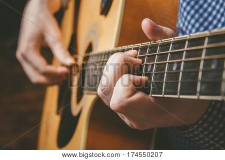 Close up of guitarist hand playing acoustic guitar
